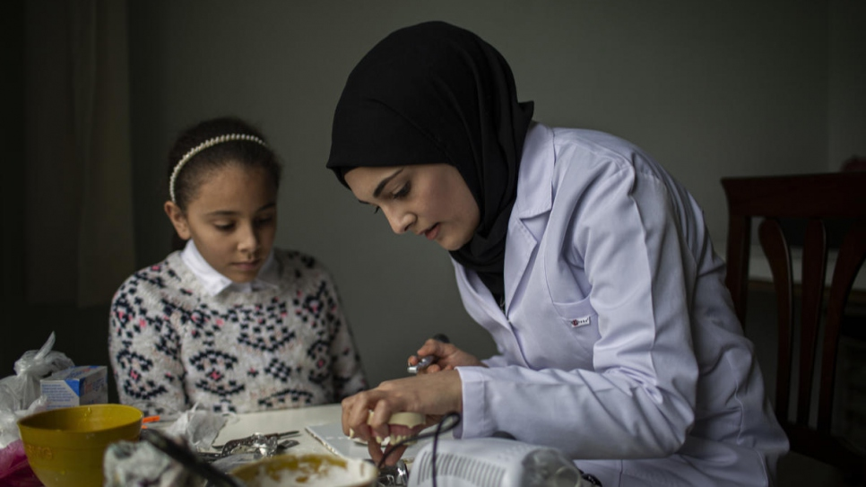 Sidra practices her dentistry skills at home while her younger sister Isra looks on.