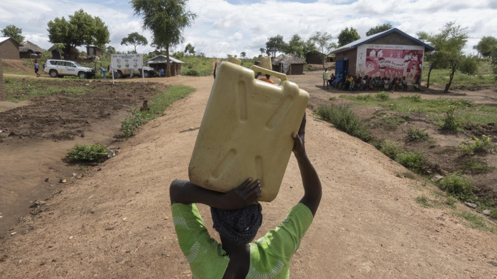 South Sudanese refugee Asha Rose Sillah carries a jerrycan of water from a water point to her home in Bidibidi refugee camp, Uganda.