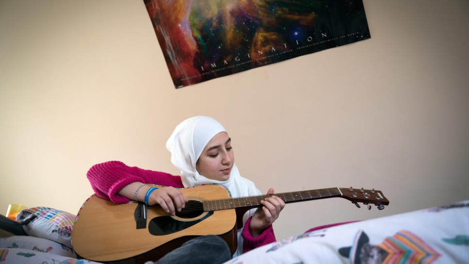 Maya Ghazal plays guitar at home in her room.
