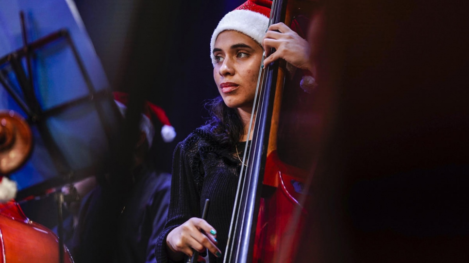 Vanessa Rivas, a Venezuelan-born member of the Philharmonic Orchestra, performs at a free Christmas concert honoring refugees and asylum seekers.