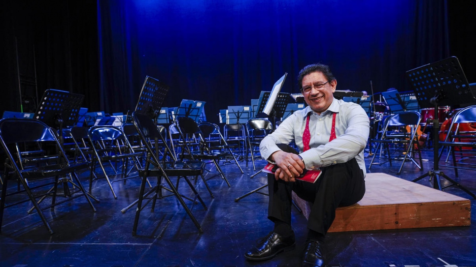 Víctor Mata, founder of the Panama Philharmonic Orchestra, on stage ahead of the group's Christmas concert dedicated to refugees and asylum seekers.