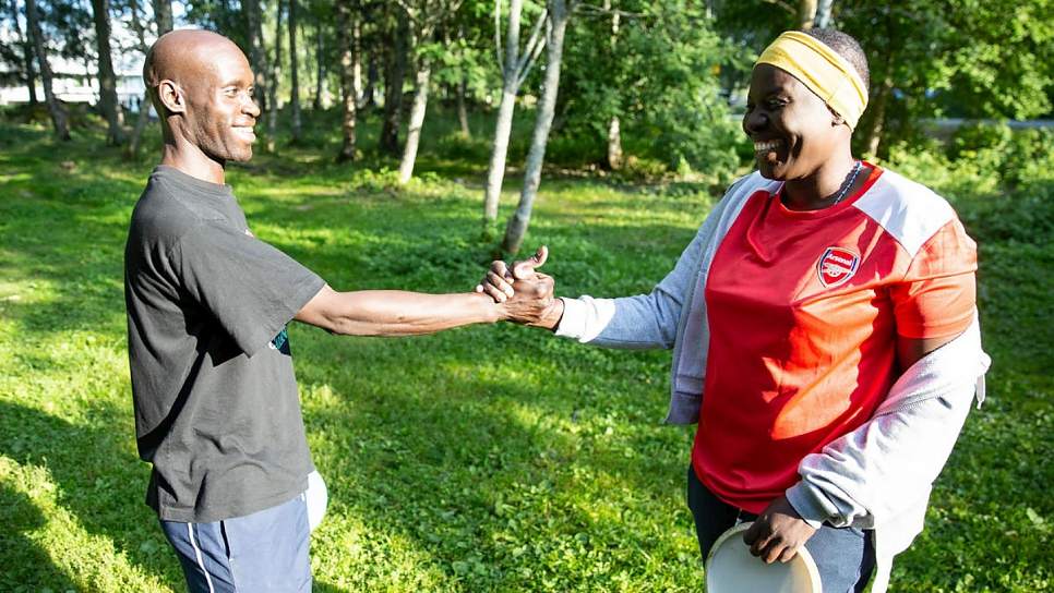 Nakout shakes hands with her friend Henry at the end of a game of frisbee golf, a popular local game she has taken up to keep fit and make friends in her new hometown of Vaasa in Finland.