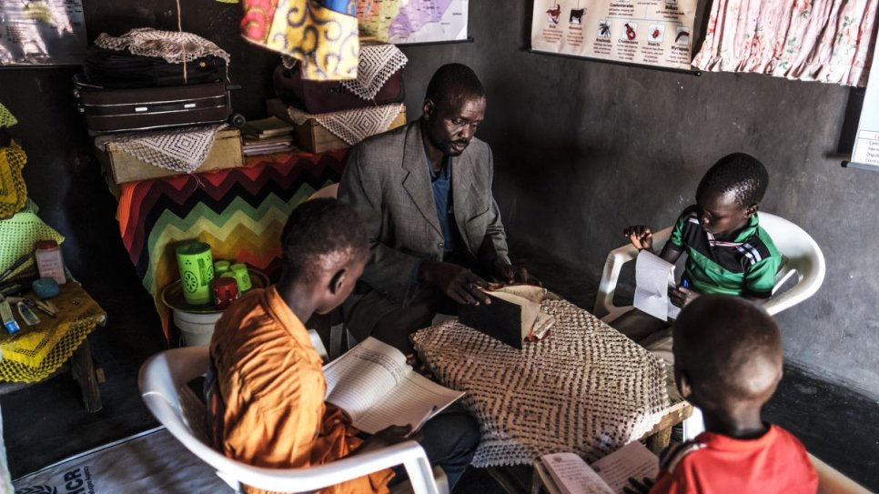 James Tut reads a book with his children at their home.
