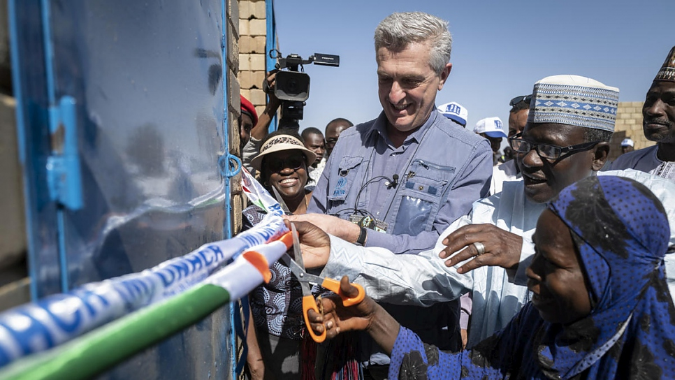 UN High Commissioner for Refugees Filippo Grandi cuts the ribbon alongside Aminatou Chekaraou, the first member of the host community to receive a brick house in Ouallam.