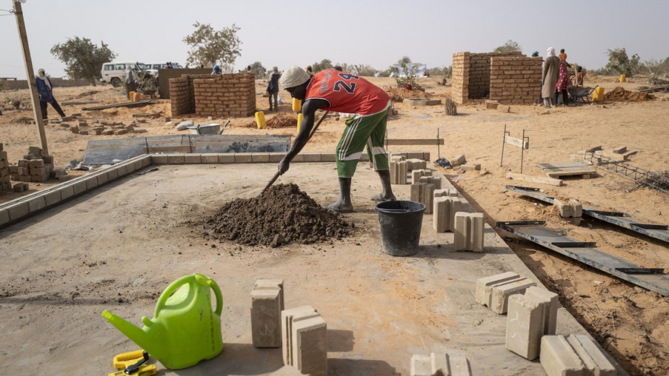 Construction workers representing both the refugee and host communities build the first of 1,000 brick homes in Ouallam village, Tillaberi, south-west Niger.