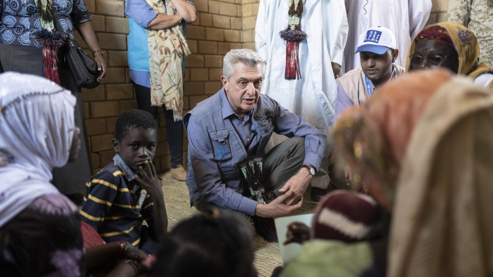 UN High Commissioner for Refugees Filippo Grandi speaks with Kadi Oumar, the widowed head of a household of nine, in her new home.