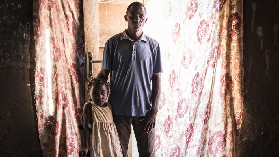 Chadrack Neta stands with his daughter in his house in Tshikapa in the Democratic Republic of the Congo. He returned with his family from Angola last October.