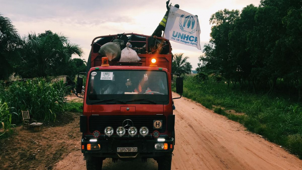 A Congolese repatriate waves the UNHCR flag as he arrives in Kananga, capital of the Kasai Province, after years spent as a refugee in Angola.