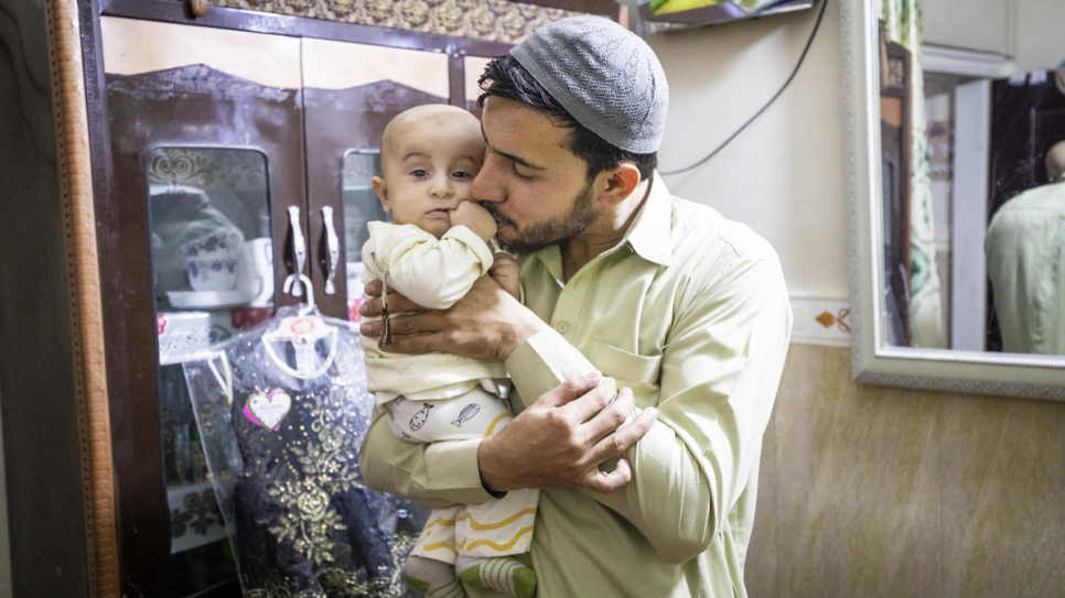 Sifat cradles his son in the small apartment where he lives with his family.
