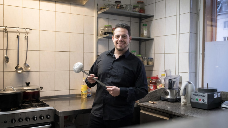 Syrian refugee Fadi Zaim, 32, in his mother Salma Al Armarchi's kitchen in Berlin, from where she runs her company, Jasmin Catering.