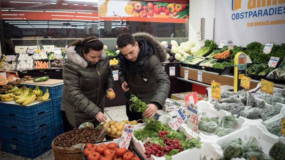 Syrian refugee Salma Al Armarchi, 53, and her son Fadi Zain, 32, buy fresh food in a Turkish supermarket near her kitchen in Berlin.