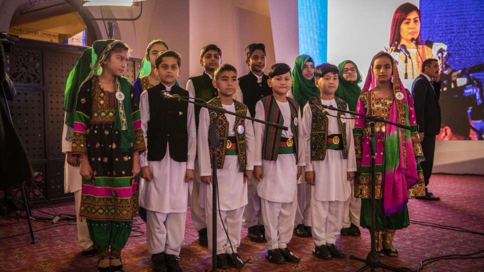 Afghan and Pakistani children in traditional national dress sing the national anthems of both countries at the start of the Refugee Summit in Islamabad.