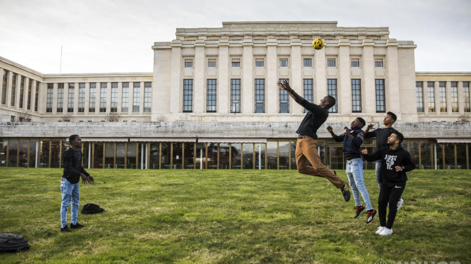 Refugees and asylum-seekers attending events during the Global Refugee Forum play football on the lawn at the Palais des Nations.