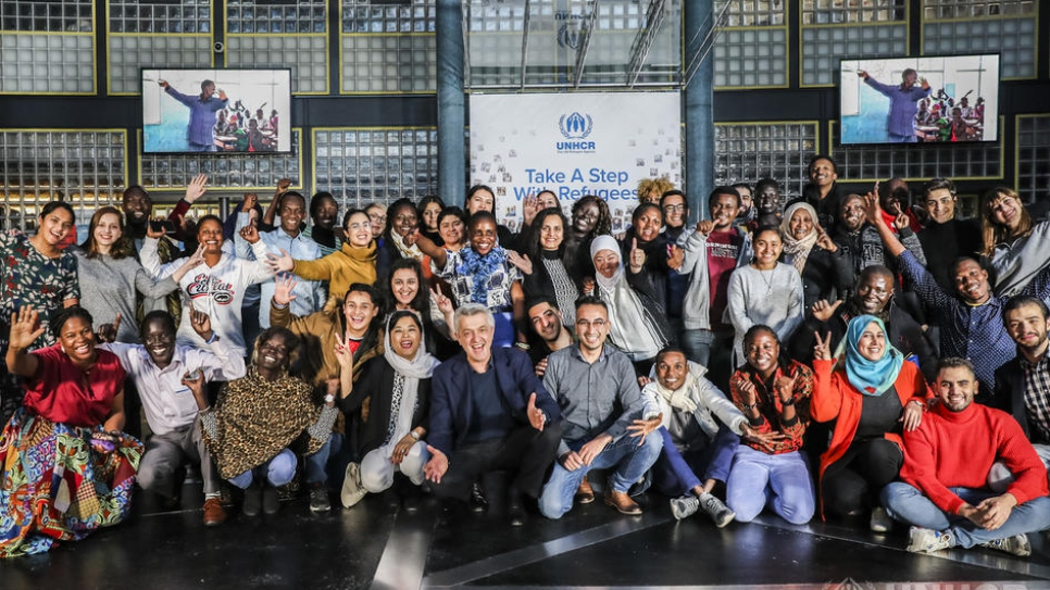 UN High Commissioner for Refugees Filippo Grandi (front-centre, crouching) meets a group of 70 young refugees attending the Global Refugee Forum in Geneva.