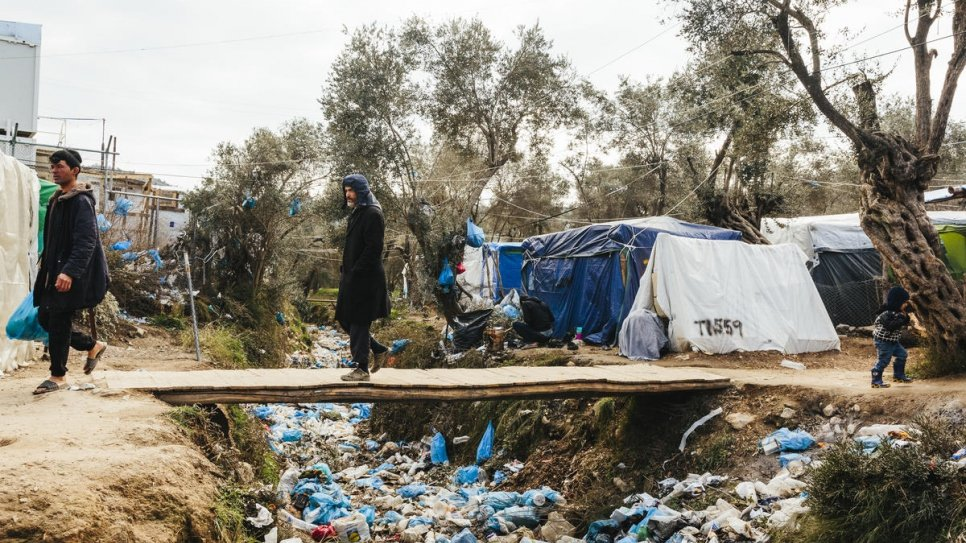 A man crosses a dry river full of garbage at a makeshift camp adjacent to the Moria reception and identification centre on the Greek island of Lesvos.