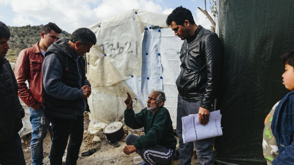 Sardar (centre-left) speaks with Abdul What Qadiri (sitting), a 65-year-old Afghan asylum-seeker who has cancer, at the Moria reception and identification centre on Lesvos.
