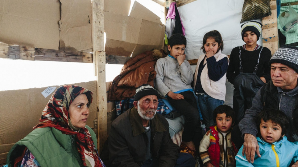 Sardar (right) sits in his small wooden hut on Lesvos, joined by his children, mother-in-law and father-in-law, who is blind and had to be carried on the journey to Greece.