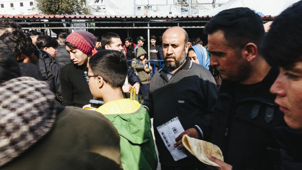 Asylum-seekers and migrants wait at a food distribution line inside the overcrowded Moria reception and identification centre on the Greek island of Lesvos.
