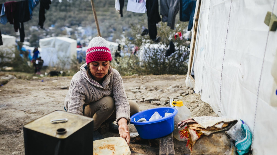 Fahima, who fled Afghanistan with her husband and five children, bakes flatbread in a makeshift oven outside the family's hut among the olive groves near the Moria reception and identification centre.