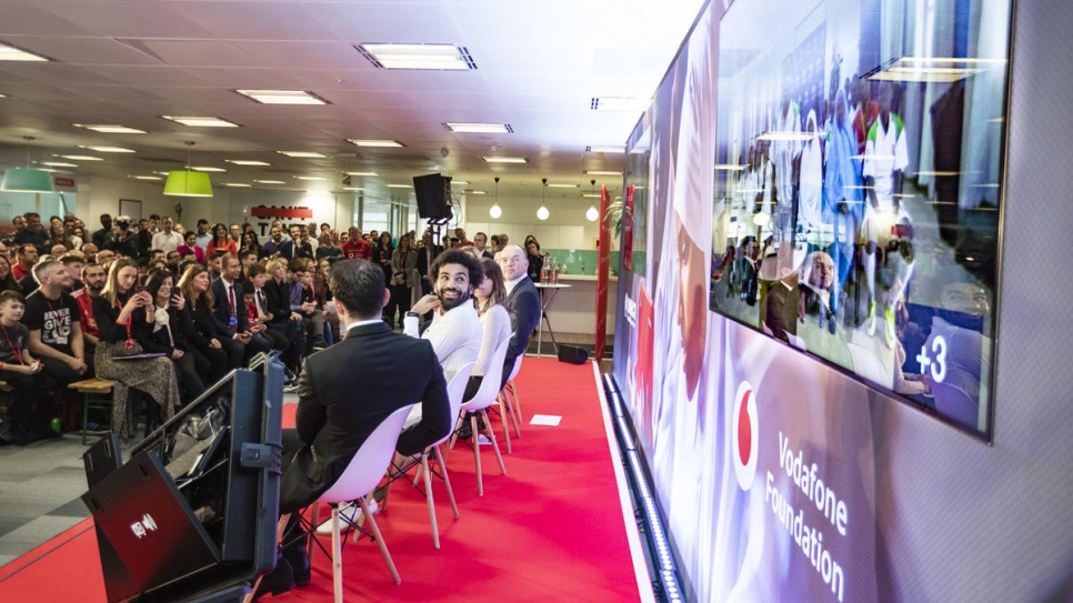 Football star Mohamed Salah glances at a TV screen at an event in London during which he was announced as the first Ambassador of Instant Network Schools.