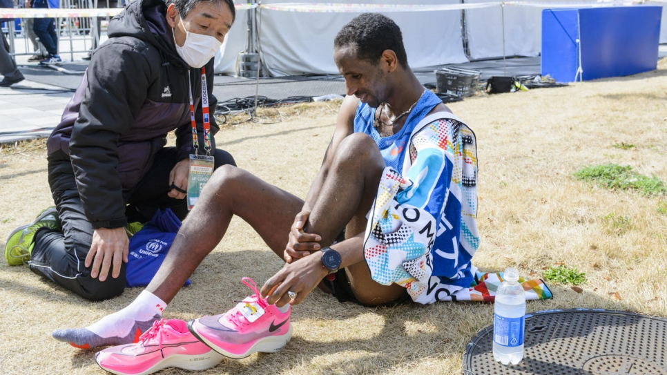 Yonas removes his shoes to ease his swollen feet after more than two hours of racing.