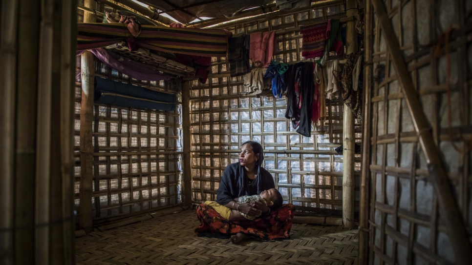 Rahima Khatun holds her son Mohammad Arafat as he sleeps in their shelter in Camp 1 West, Kutupalong, Cox's Bazar, Bangladesh.