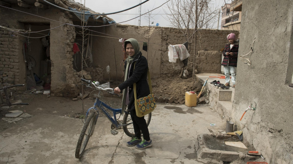 Twenty-seven-year-old Afghan returnee Kobra Yusufy checks her bicycle before leaving for class in Kabul, Afghanistan.