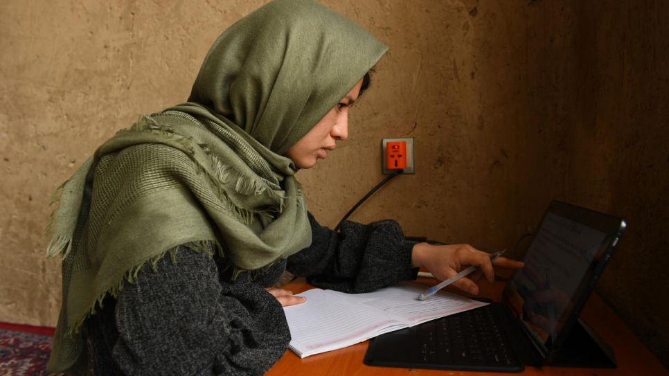 Twenty-seven-year-old Afghan returnee Kobra Yusufy studies at home in Kabul, Afghanistan.