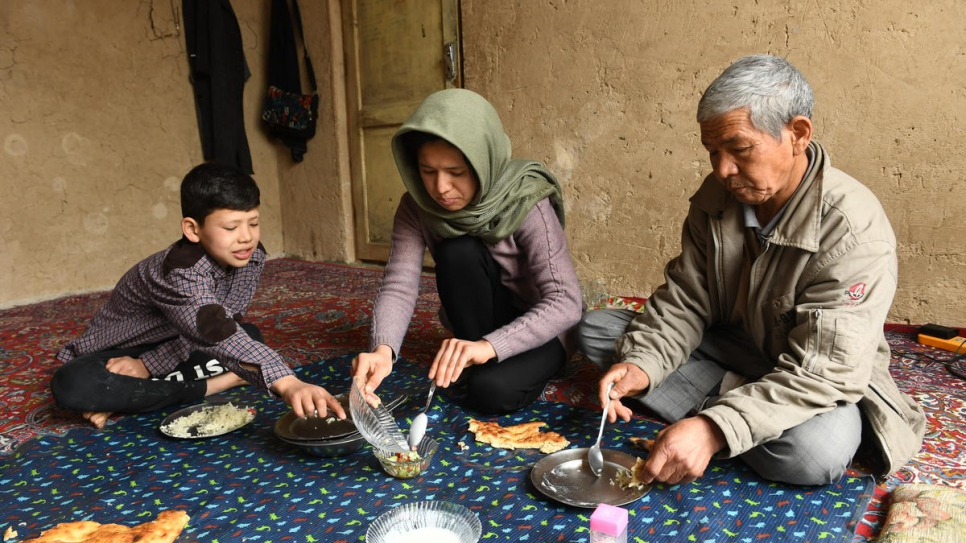 Twenty-seven-year-old Afghan returnee Kobra Yusufy eats lunch with her brother Mahdi, 11, and father Mohammad, 56, in their living room in Kabul.