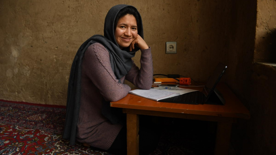 Twenty-seven-year-old Afghan returnee Kobra Yusufy is photographed at home in her living room in Kabul, Afghanistan.