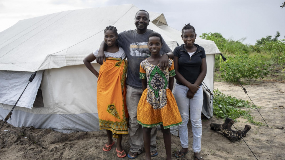 Jose Martinho, 43, poses with his wife Angelina, 31, and their daughters Laura, 12, and Luiza, 14, in front of their tent in Mutua settlement, which hosts some 700 people. They were relocated there after Cyclone Idai a year ago.