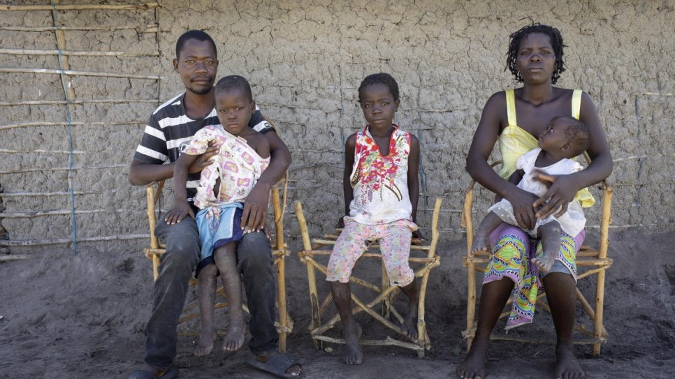 Amelia, her husband Almeida Juoa, 34, and their children Rosa, 8, Elias, 4 and Alsofina, who is one year old, pose in front of their home in Savane settlement. They were relocated there by the government after Cyclone Idai a year ago.