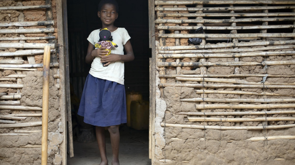 Congolese refugee Nadine, 9, holds one of the dolls made by her mother, Kituza, in Maratane camp, Mozambique.