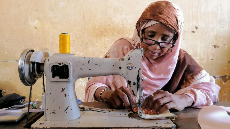 Fatouma, a refugee from Mali, uses a sewing machine to make face masks at a workshop in Niamey.