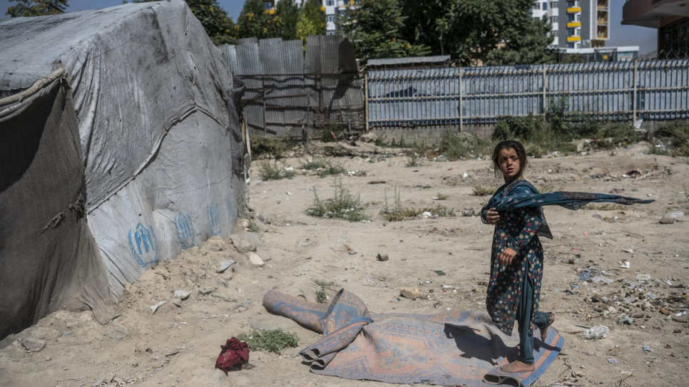 A child walks through a camp for internally displaced people in the Afghan capital, Kabul, July 2019.