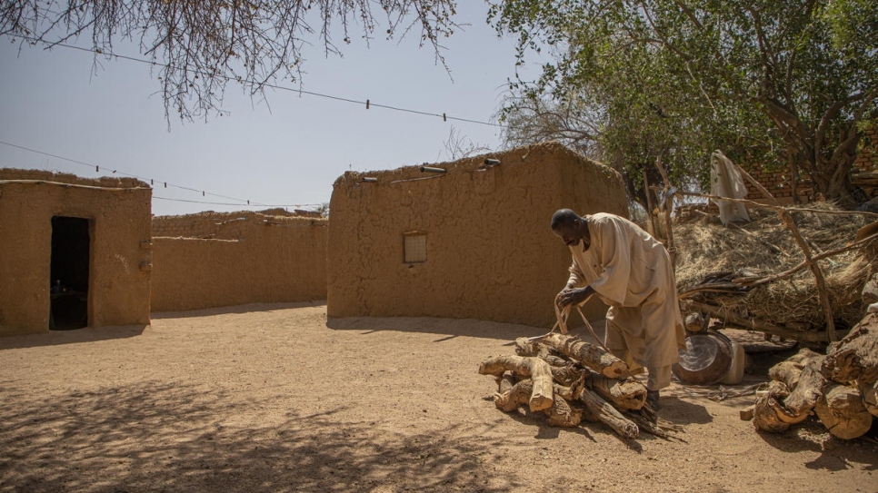 Ahmed Ishag Babiker, 54, piles up firewood in his compound in Kabkabiya in North Darfur, Sudan. He and his family were displaced when armed militias attacked his village in Wadi Bare in 2004.