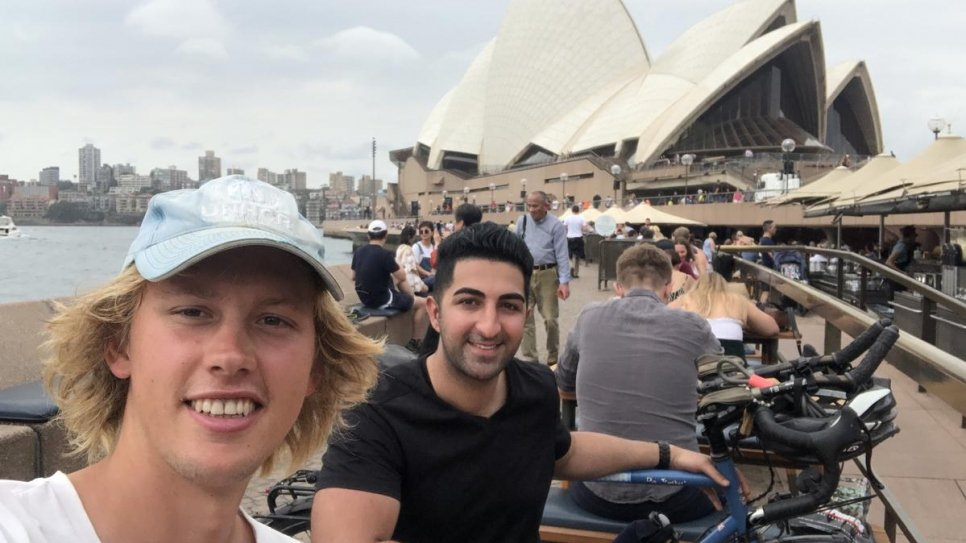 Cyclist Theo Foster meets Iranian refugee and co-chair of UNHCR's Global Youth Advisory Council, Arash Bordbar at Sydney Opera House, Australia.