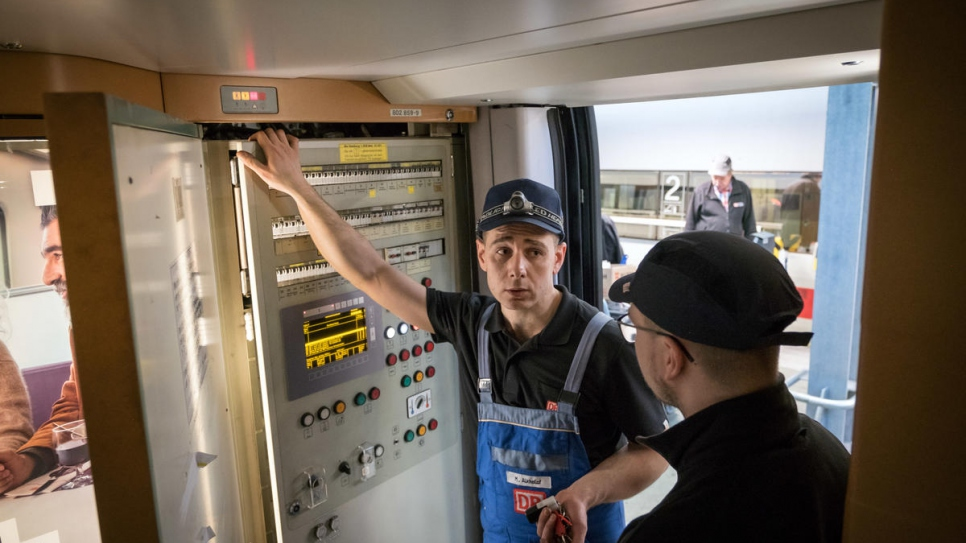 Syrian refugee Mohammad Alkhalaf (left) and his German colleague Dominik Otte, check the electrics of an Intercity Express (ICE) high-speed train, as part of an engineer training programme with Deutsche Bahn.