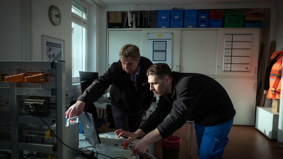 Syrian refugee Mohammad Alkhalaf (right) has a theory lesson with his trainer Klaus Holzhauer in Hamburg, where he is training to be an engineer with Deutsche Bahn.