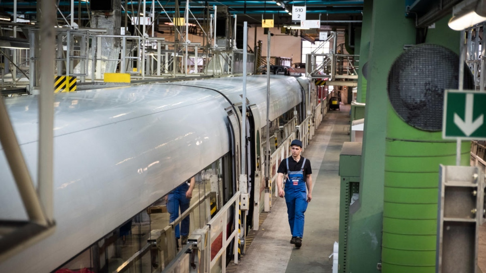 Syrian refugee Mohammad Alkhalaf walks through Deutsche Bahn's Hamburg-Eidelstedt depot, where he is training to be an engineer.