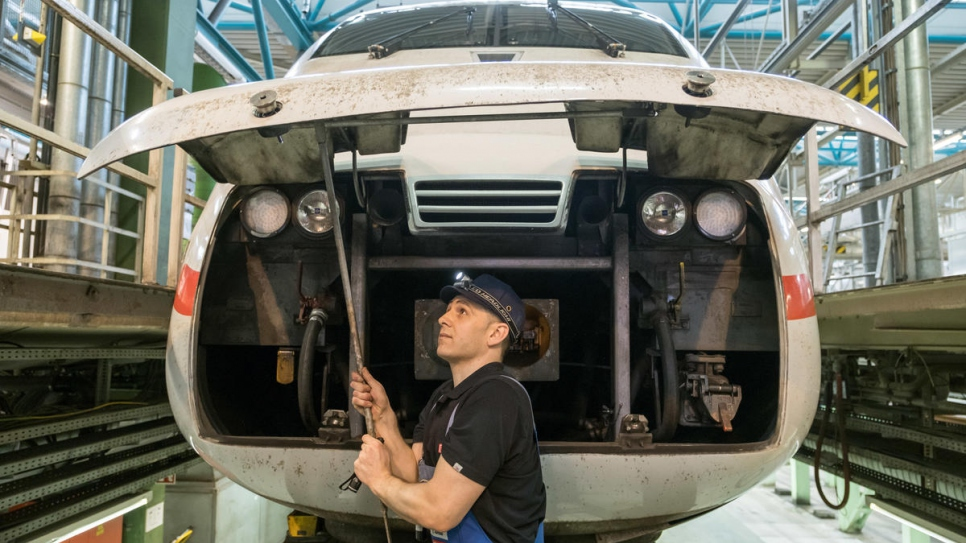 Syrian refugee Mohammad Alkhalaf checks the railcar of an Intercity Express (ICE) train at Deutsche Bahn's Hamburg-Eidelstedt depot, where he is training to be an engineer.