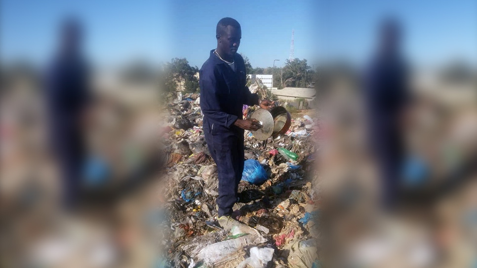 Sudanese refugee Mohammed looks for recyclables at a waste landfill in southern Tripoli, Libya.