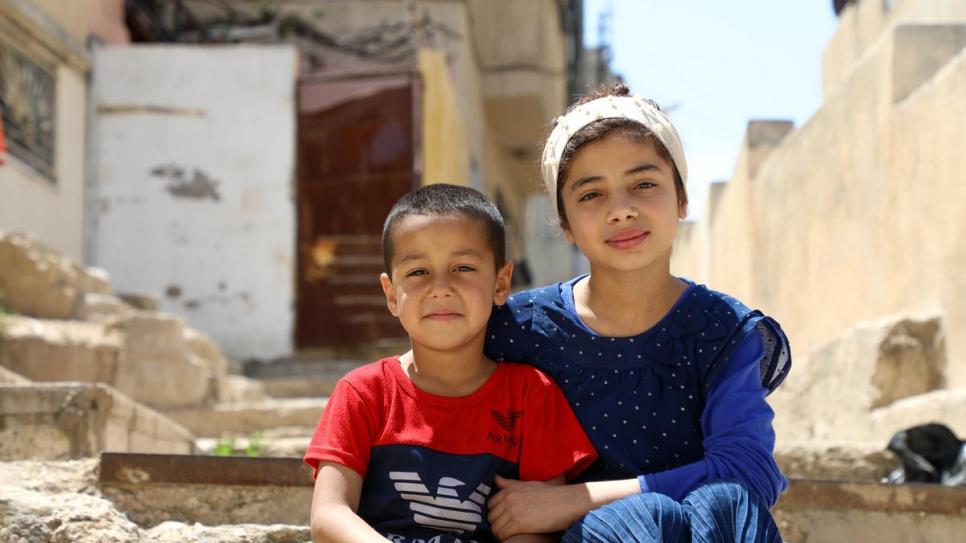 Nadia, 12, and her youngest brother Abed, 5, sit in the alleyway outside their home in East Amman. They and their three other siblings have been taking turns using the family's one TV and mobile phone.