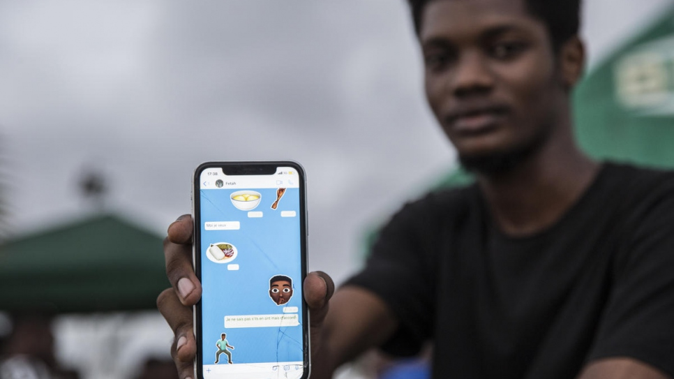 Ivorian graphic designer O'Plérou displays some of the emojis he has designed.