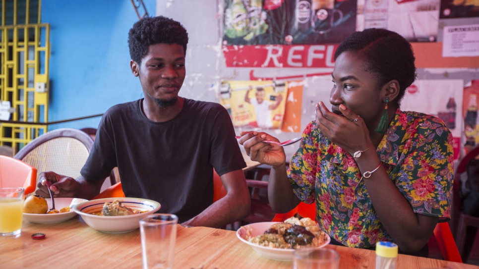 Ivorian graphic designer O'Plérou enjoys a traditional meal with a friend at a popular food joint in Abidjan, Côte d'Ivoire.