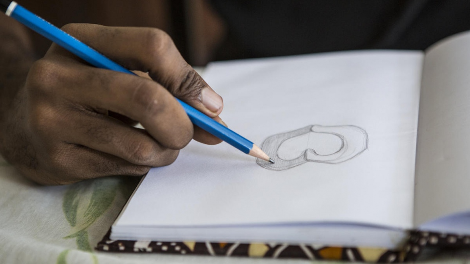 Ivorian graphic designer O'Plérou sketches the design of the World Refugee Day 2020 emoji on paper before he moves to the computer.