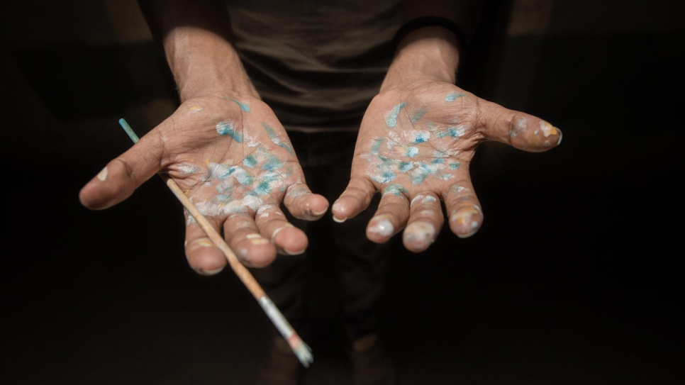 Solomon displays his paint-spattered hands after working in the art room that he shares with other residents.