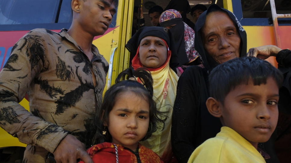 Rohingya refugees alight from a bus at the UNHCR registration and distribution centre in Kutupalong settlement, Bangladesh.