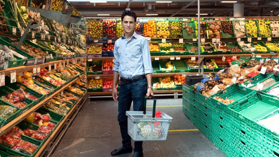 Shadi Shhadeh shops at a supermarket in Geneva, Switzerland. With fellow Syrian refugee volunteers, he delivers food and supplies to vulnerable people who are shielding from the coronavirus.