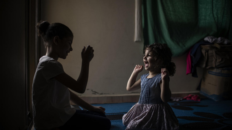 Layan, 10, plays a game with her younger sister Yasmine, 3.